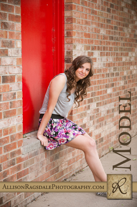 senior pic with red door and brick wall