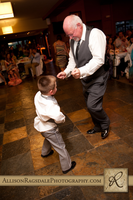 father of the groom dancing at wedding reception with ringbearer
