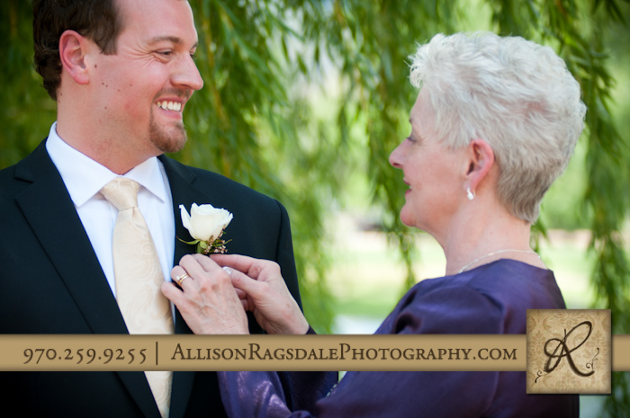 mother putting boutonniere on son and groom