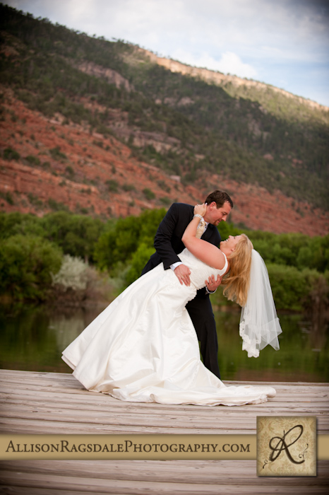 bride and groom dip with red cliffs in background