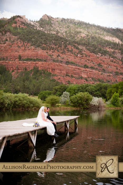 bride and groom sitting on dock at animas valley sleeping beauty ranch in durango