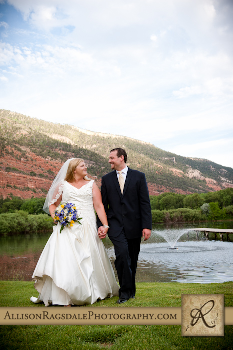 bride and groom walking with lake in background with fountain