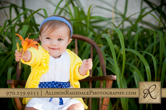 baby girl in white sundress with yellow sweater and orange day lilly