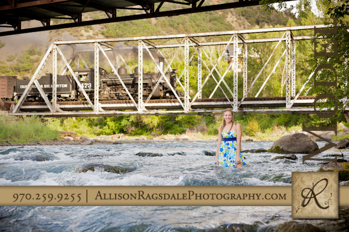girl in dress standing in river under train bridge