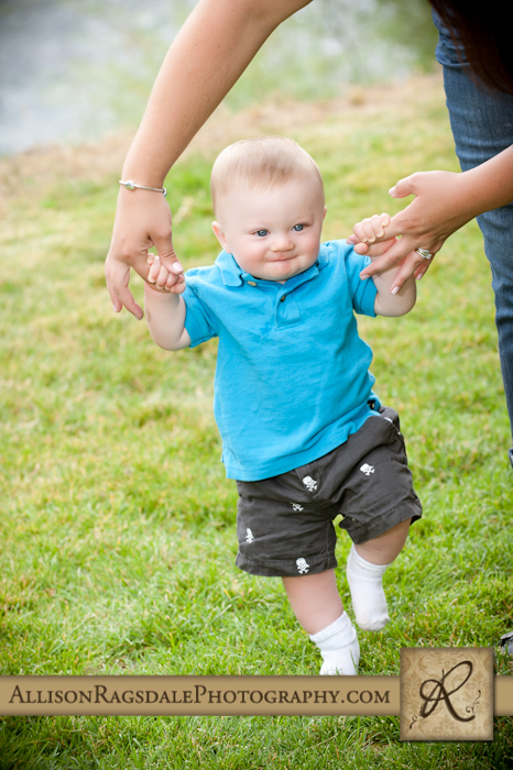 baby boy walking holding mom's hands