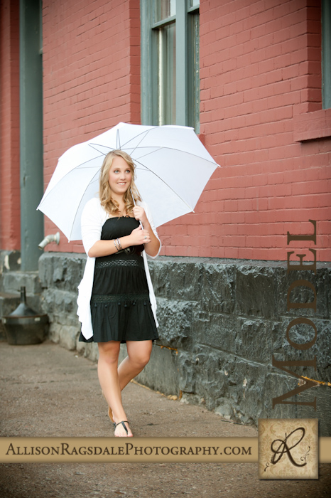 senior pictures in the rain with a white umbrella downtown durango