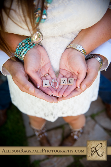 """love"" spelled with scrabble letters and an engagement ring"