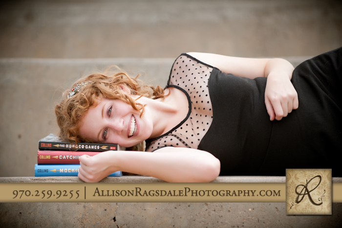 girl senior pics with hunger games trilogy in durango