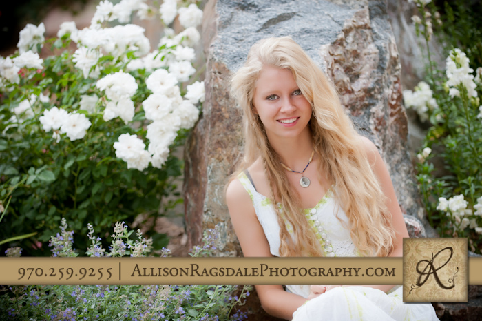 long blonde hair in rocks and white roses senior picture durango
