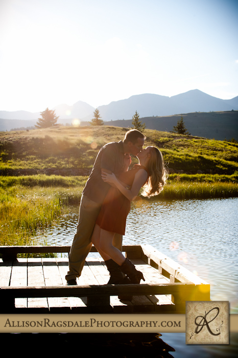 engaged couple kissing in sun flare by andrews lake