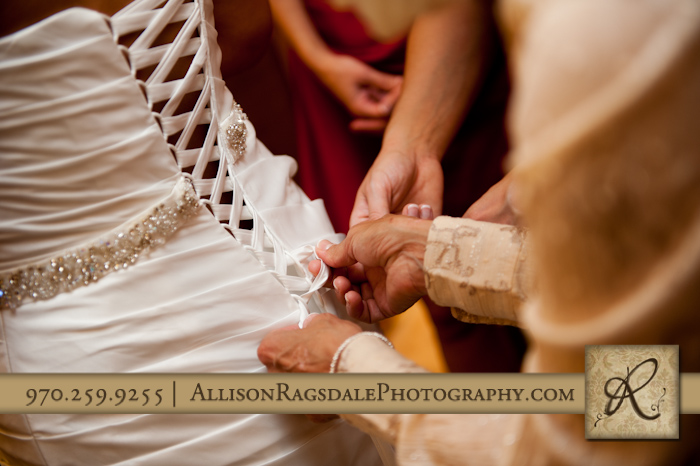 mother helping daughter with her wedding dress for wedding at the glacier club in durango co
