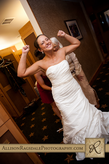 beautiful excited bride getting dressed for wedding ceremony at the glacier club in durango co