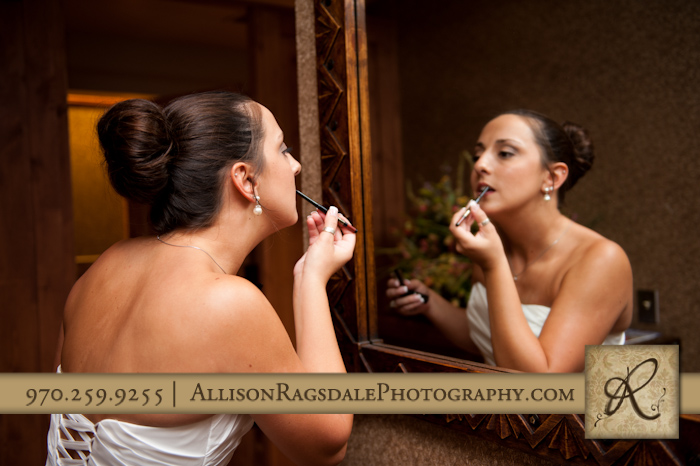 bride putting finishing touches on in mirror at the glacier club in durango co