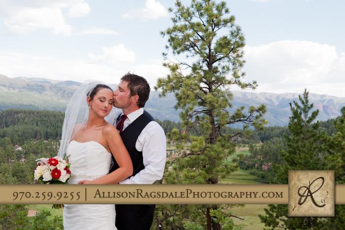 groom kisses bride on temple at durango wedding at the glacier club