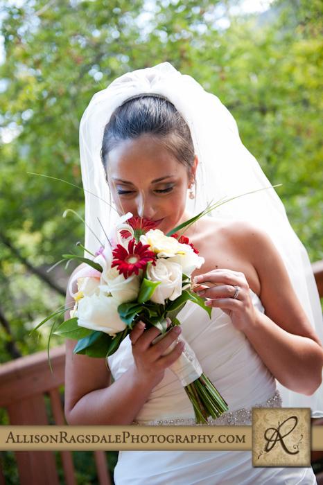 bride smells bouquet at glacier club wedding in durango