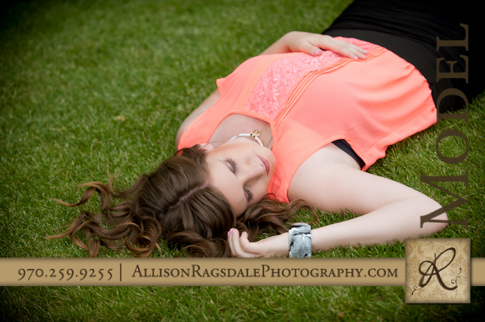 beautiful high school senior laying in green grass in durango park picture