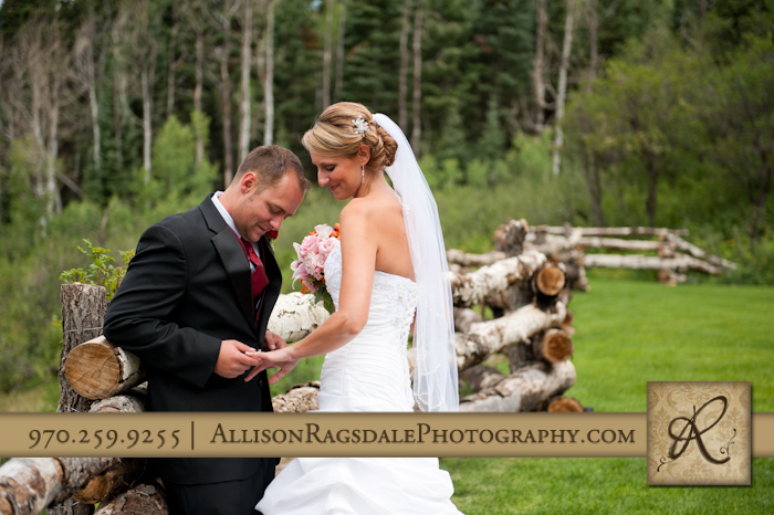 groom looking at bride's ring after wedding ceremony at thunder ridge durango co