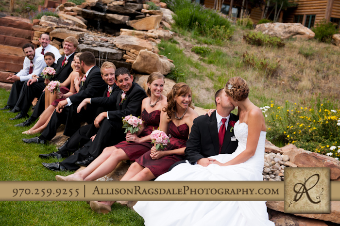 wedding party sitting on steps by waterfall at thunder ridge durango co