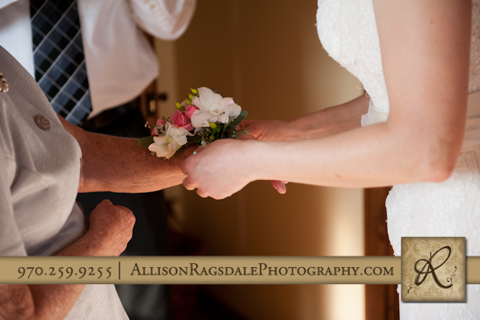 bride putting corsage on grandmother at blue lake ranch hesperus co