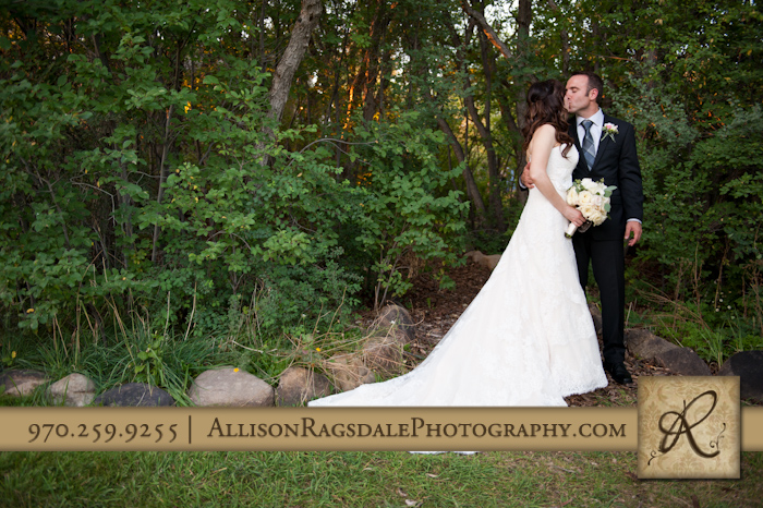 bride and groom kissing at end of path at blue lake ranch durango co