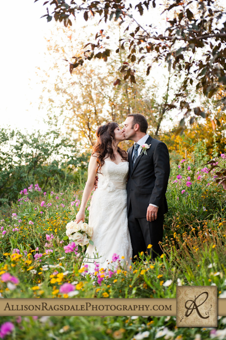 bride and groom kissing in flowers at blue lake ranch durango co