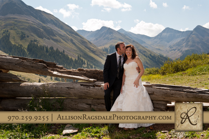 bride and groom on fence in animas forks