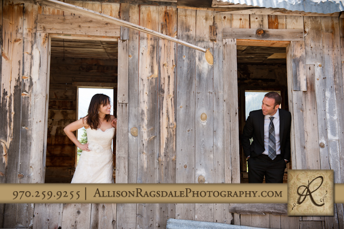 bride and groom peeking out windows in old building in animas forks silverton