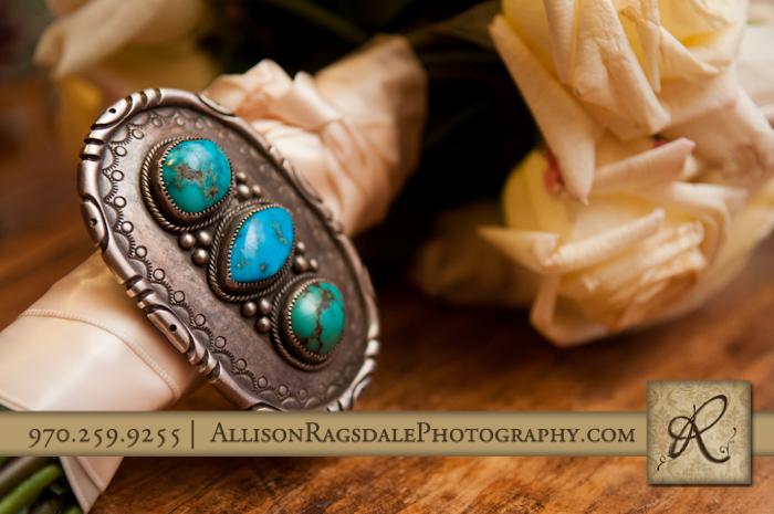 grandpas belt buckle on bridal bouquet at blue lake ranch wedding reception