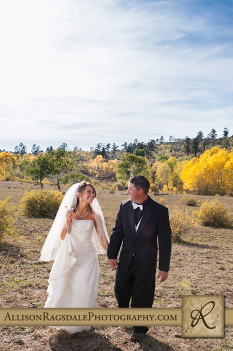 bride and groom walking through aspen grove together picture colorado
