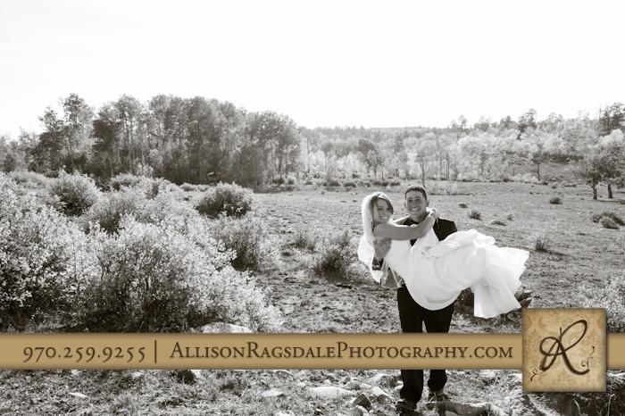 groom carrying bride through field mancos co