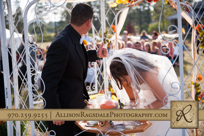 groom gives guests thumbs up as bride signs marriage license during wedding ceremony