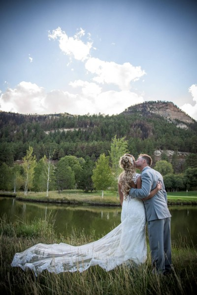 Bride and Groom portrait in front of pond in Durango CO, back of lace wedding dress, groom kissing bridge on cheek