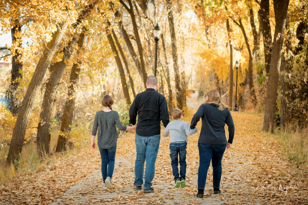 Family walking in fall leaves