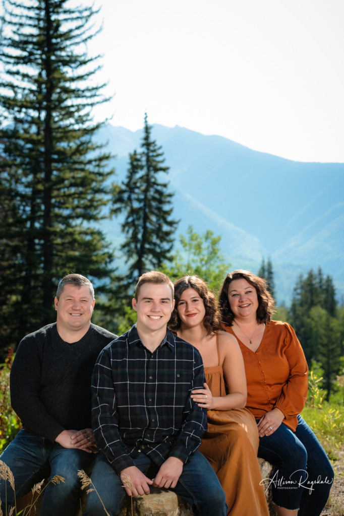 family picture sitting on rock with mountains and pine trees