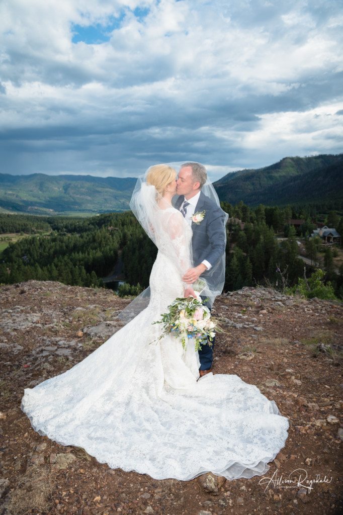 dramatic sky colorado bride and groom under veil wedding portrait