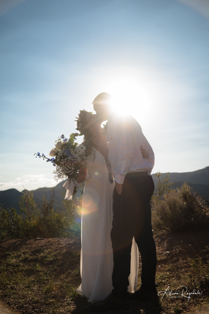 sun flare wedding couple kissing picture with bouquet