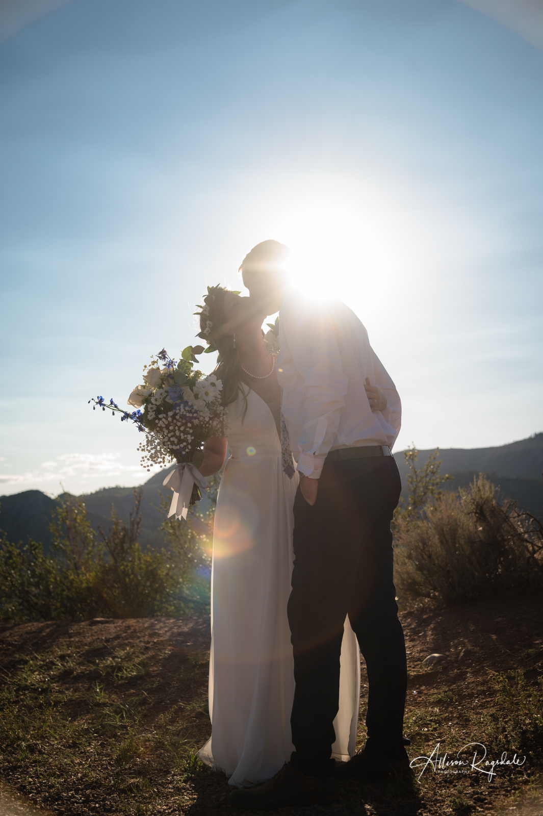 sun flare wedding couple kissing picture with bouquet at lions den