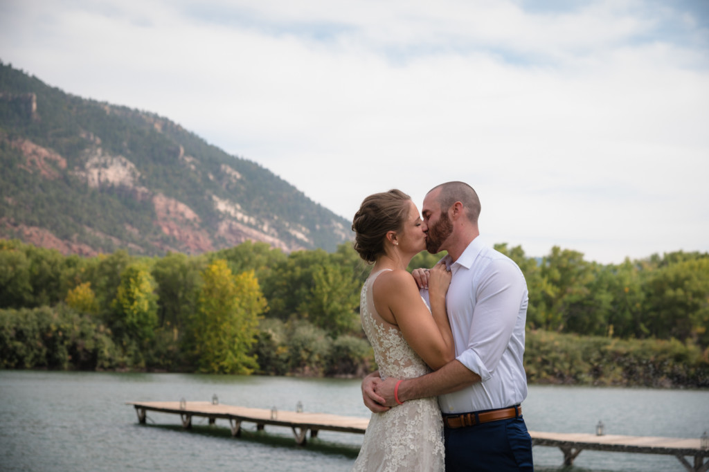 bride and groom kiss at river bend ranch durango co wedding picture with dock in background