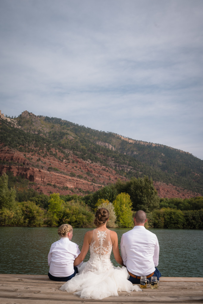 bride, daughter, and groom sitting on end of dock at river bench ranch wedding durango colorado