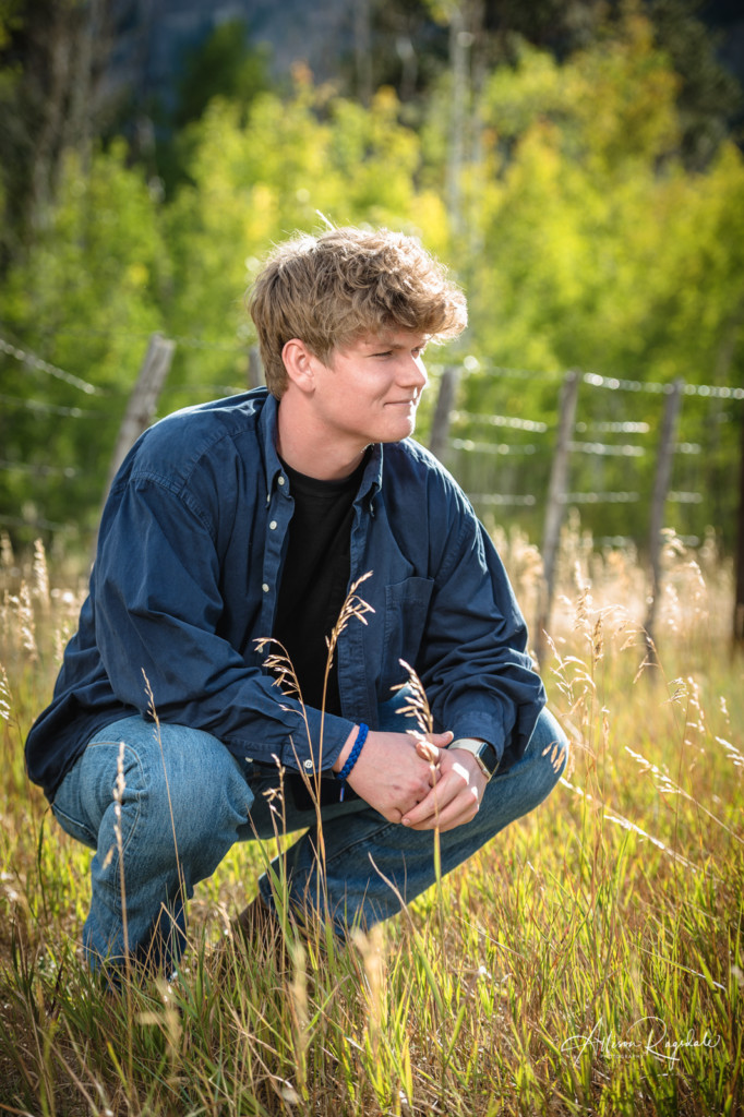 senior guy crouching in long grass picture