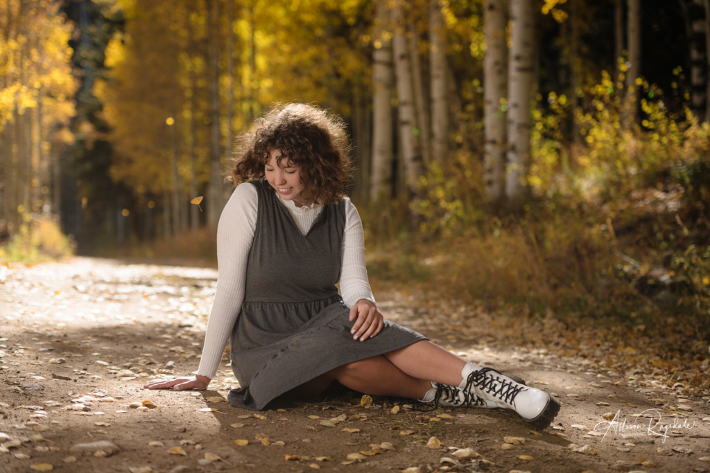 senior picture girl sitting on dirt road with aspen leaves falling around her