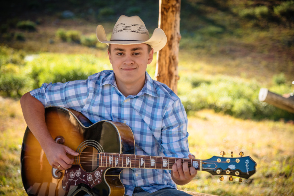 country senior picture male in cowboy hat playing guitar