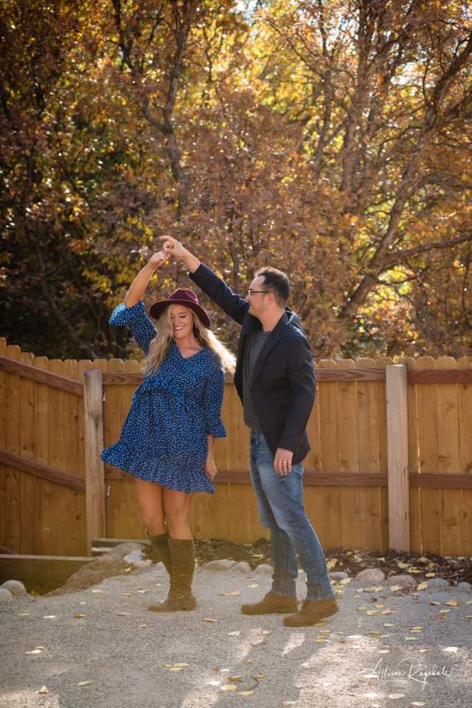 couple dancing in backyard portrait with burgundy hat
