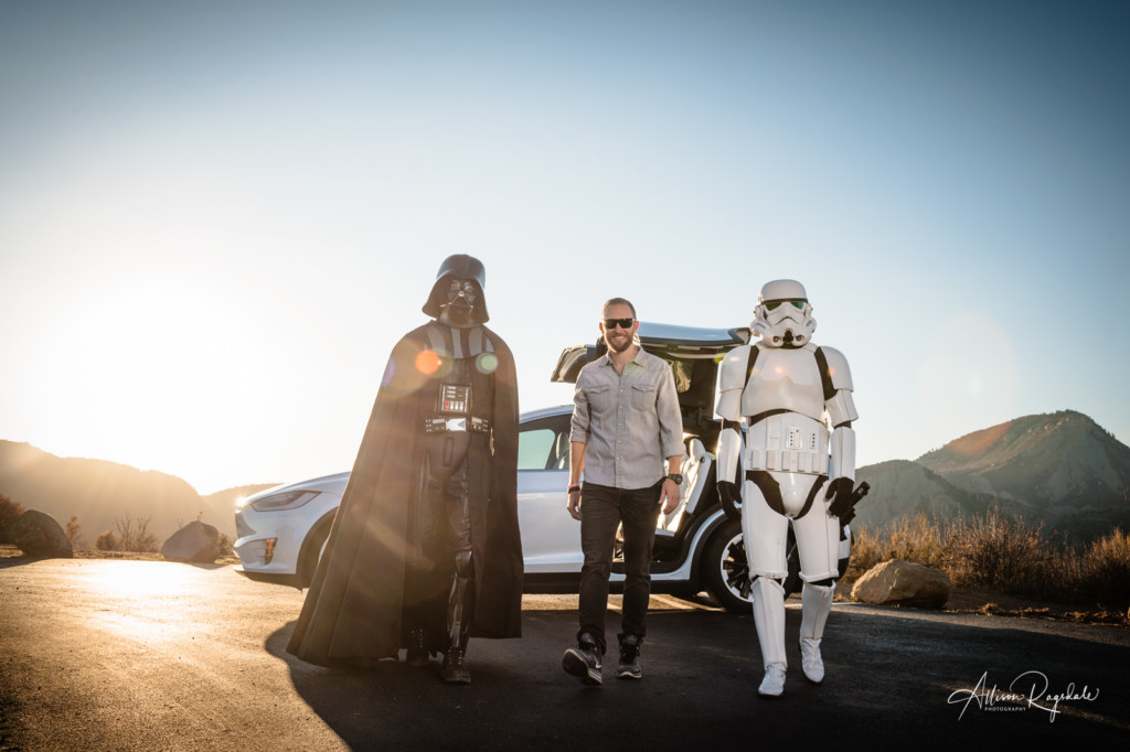 darth vader, hank blum, and a stormtrooper walking away from a tesla photo