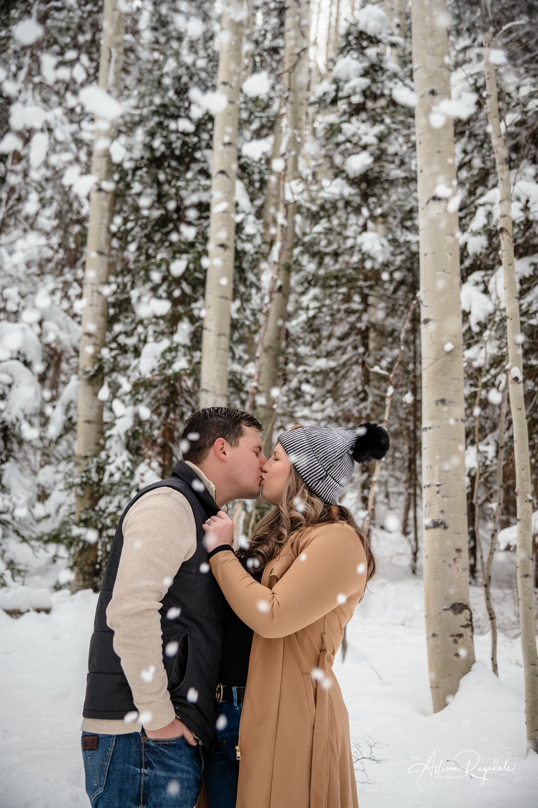 couple kiss in the snowy forest colorado portrait