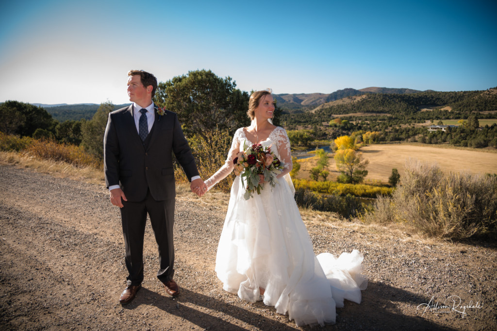 bride and groom standing in dirt road holding hands photograph