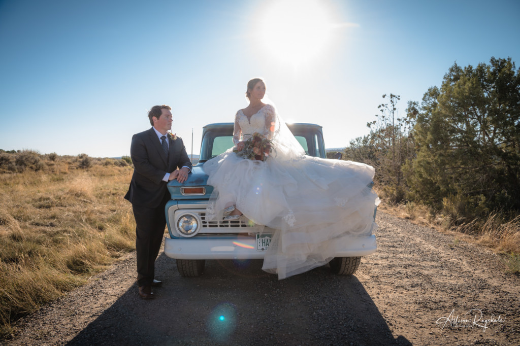 bride and groom sitting on old truck backlit picture