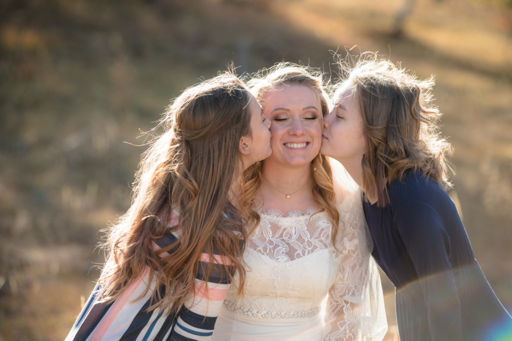 daughters kissing bride on cheeks picture
