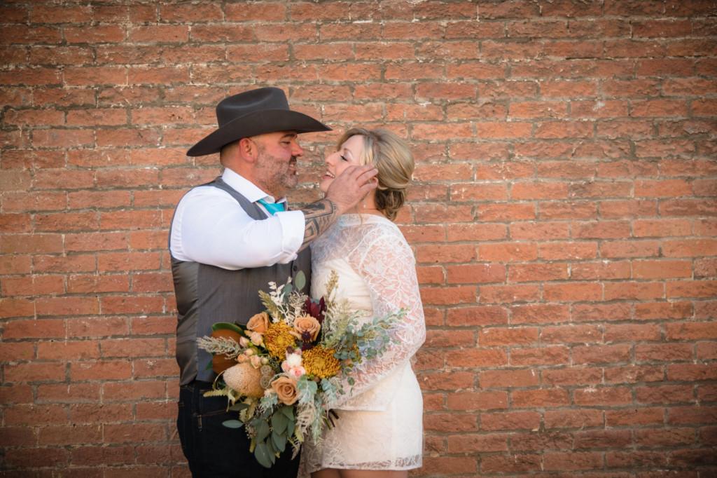 bride and groom brick wall downtown durango co portrait