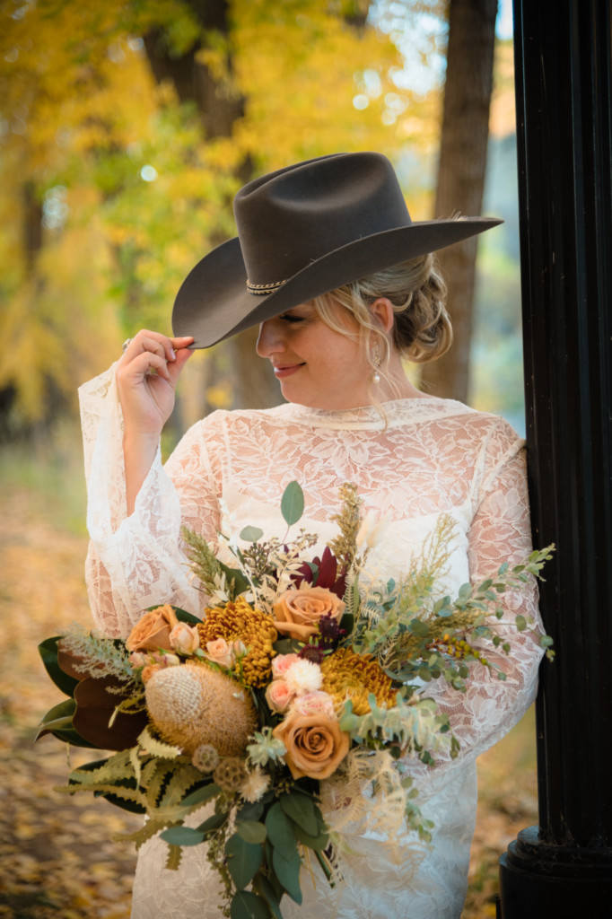 bride wearing groom's cowboy hat lace dress fall leaves portrait